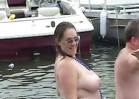 Party girls take off their bikini tops on boats at the lake
