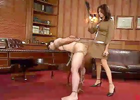 Sexy brunette toys her sex slave in the ass in an office